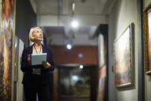 Portrait Of Mature Woman Holding Clipboard Looking At Paintings Standing In Art Gallery Or Museum, Copy Space