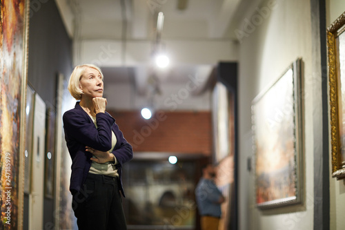 Fotografiet  Portrait of pensive mature woman looking at paintings standing in art gallery or