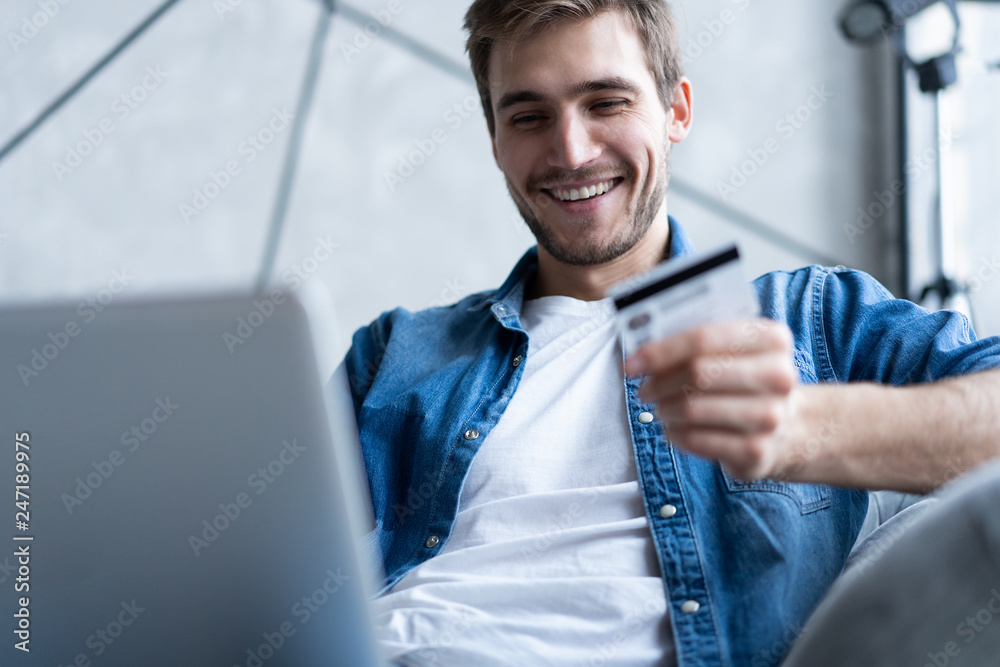 Fototapeta technology, shopping, banking, home and lifestyle concept - close up of man with laptop computer and credit card at home.