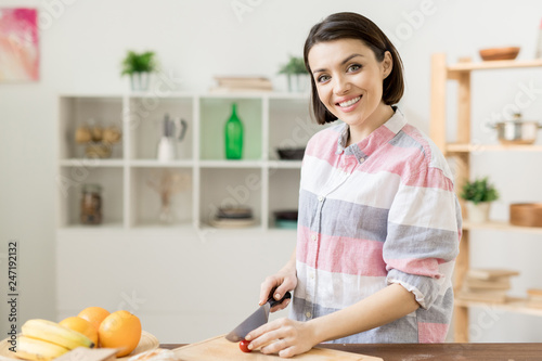 Young cheerful pretty woman cutting fresh cherry tomatoes on wooden board while cooking vegetable salad in the kitchen