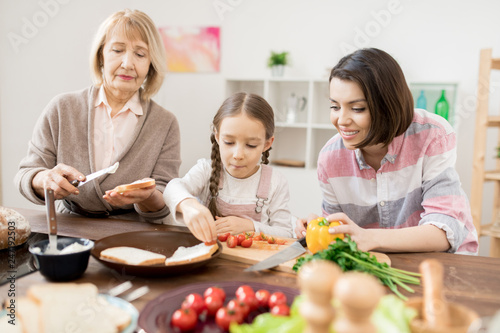 Two women and little girl preparing sandwiches with vegetables and spread cheese for breakfast