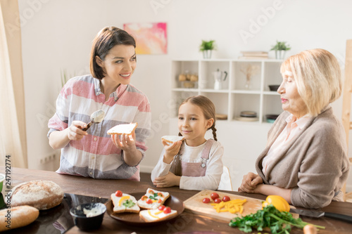 Young woman making sandwiches for breakfast and talking to her mom in the kitchen with little daughter eating near by