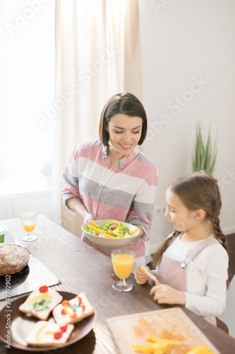 Young woman with fresh homemmade vegetable swalad offering her little daughter to eat it for breakfast