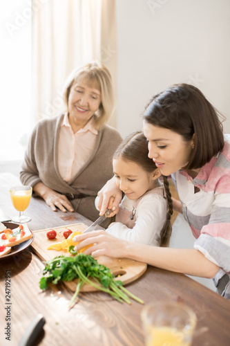 Young woman teaching her little deaughter to cut capsicum while cooking vegetable salad in the kitchen