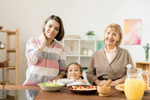Two happy women and little girl looking at you while going to prepare festive healthy dinner