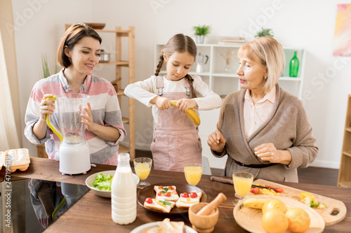 Little girl taking peel off banana while helping her mom and grandma with fruit smoothie for breakfast