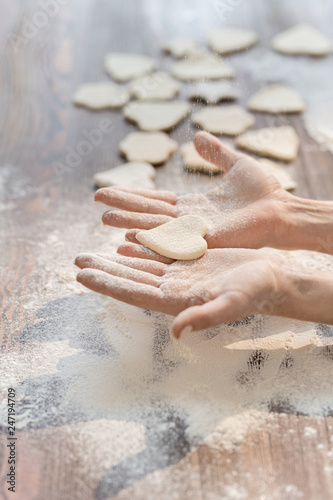 Hands of woman holding one of raw cookies in shape of heart while cooking homemade pastry