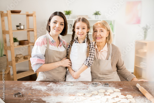 Three happy housewives in aprons standing by kitchen table with flour and raw cookies while making homemade pastry