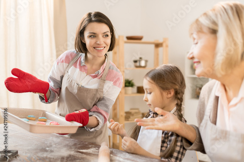 Pretty young housewife with hot tray showing her mother and daughter fresh baked cookies