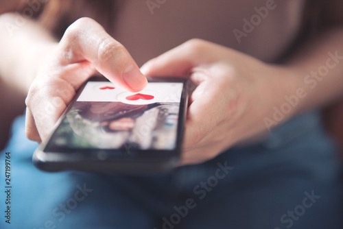 Finger of woman pushing heart icon on screen in mobile smartphone application. Online dating app, valentine's day concept.