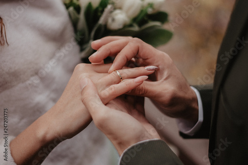 Fotografía  Groom wears golden wedding ring on the bride finger