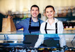 Young man and woman standing behind the counter of a restaurant. Kitchen behind