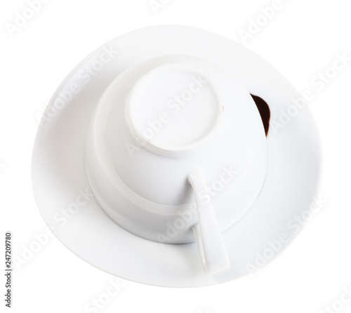 flipped cup with carob grounds on saucer isolated