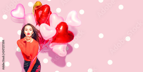 Valentine's Day. Beauty girl with colorful air balloons having fun over pink polka dots background