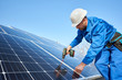 Leinwanddruck Bild Man worker in blue suit and protective helmet installing solar photovoltaic panel system using screwdriver. Professional electrician mounting blue solar module. Alternative energy ecological concept.