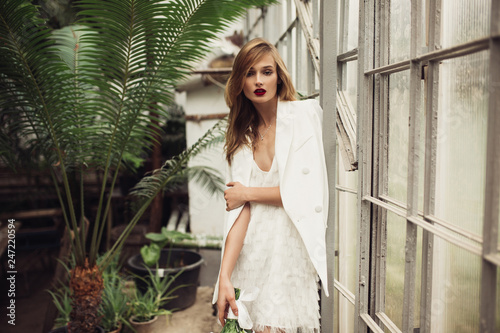 Photo  Young beautiful woman in white jacket and dress thoughtfully looking in camera n