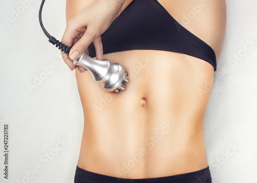 Fototapeta  The doctor does the Rf lifting procedure on the stomach and hips of a woman in a beauty parlor