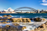 sydney harbour view with opera house, bridge and rocks in the foreground