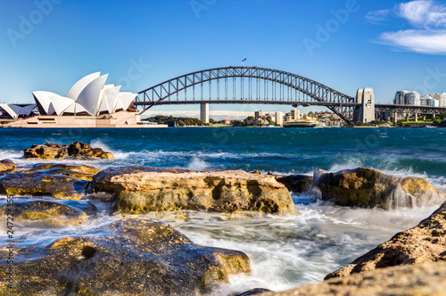 sydney harbour view with opera house, bridge and rocks in the foreground Canvas Print