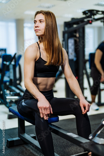Pretty sexy fitness woman with perfect muscular body resting