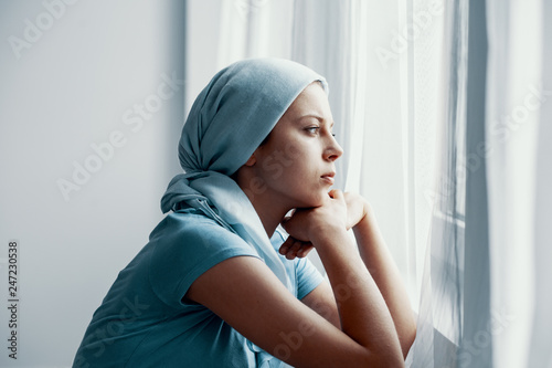 Fotografía  Thoughtful young girl suffering from bone cancer, wearing blue headscarf and loo