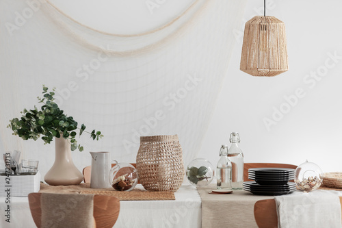 Fotografía Green plant in beige vase, white jug and wicker lantern on dining table in brigh