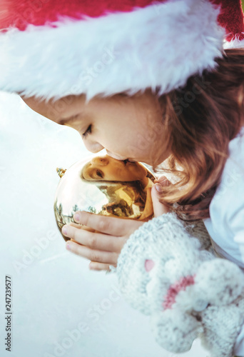 Poster Artist KB Cute little girl kissing a golden, christmas glass ball