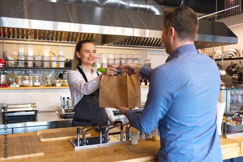 Fototapeta Waitress serving takeaway food to customer at counter in small family eatery restaurant.  obraz