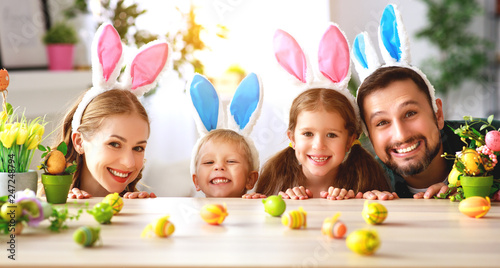 Easter. happy family mother father and children are preparing for holiday home with eggs.