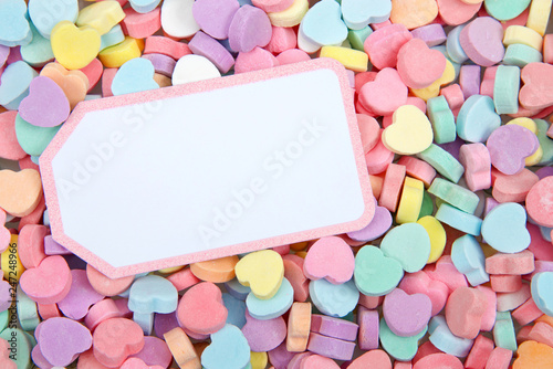 Brightly colored candy hearts, white card with pink border laying on top for copy space. Valentine's Day.
