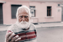 Gray Old Grandfather Points With His Finger And Looks Thoughtfully Into The Distance.