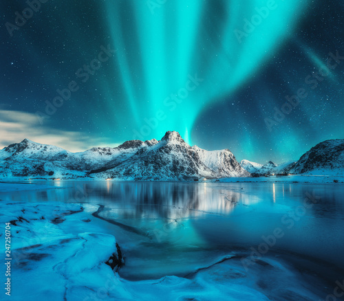 Ingelijste posters Blauwe jeans Aurora borealis over snowy mountains, frozen sea coast, reflection in water at night. Lofoten islands, Norway. Northern lights. Winter landscape with polar lights, ice in water. Starry sky with aurora