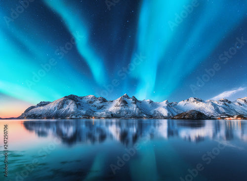 Foto auf Leinwand Insel Northern lights and snow covered mountains in Lofoten islands, Norway. Aurora borealis. Starry sky with polar lights and snowy rocks reflected in water. Night winter landscape with aurora, sea. Nature