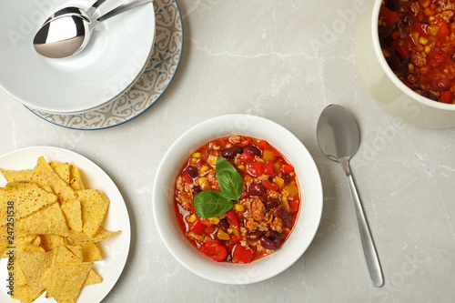 Flat lay composition with chili con carne and tortilla chips on light background