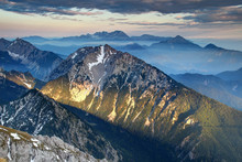 Low Evening Sunlight At Sunset Illuminates Sharp Rocky Ridges And Dark Pine Woods In Hazy Karavanke And Kamnisko Savinjske Alpe Ranges, Begunjscica Grintovec Storzic Gorenjska Kranjska Slovenia Europe