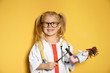 Leinwandbild Motiv Cute child imagining herself as doctor while playing with reflex hammer and doll on color background