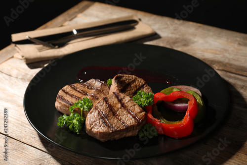 Plate with grilled meat and garnish on table