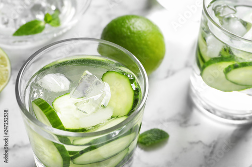 Glass with fresh cucumber water on table, closeup. Space for text