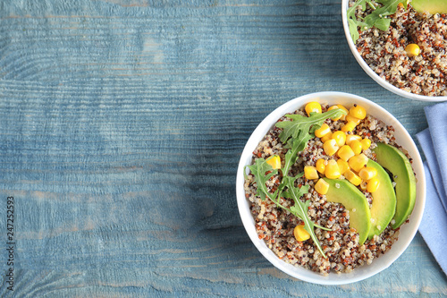 Healthy quinoa salad with vegetables in bowls on wooden table, top view. Space for text