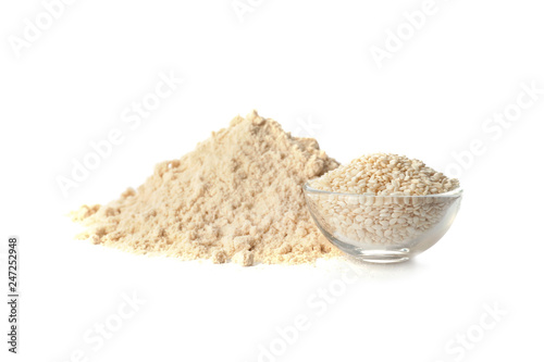 Pile of fresh flour and bowl with sesame seeds isolated on white