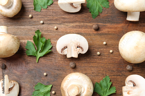 Flat lay composition with fresh champignon mushrooms on wooden background