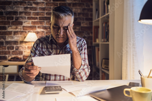 Worried man checking his domestic bills at home