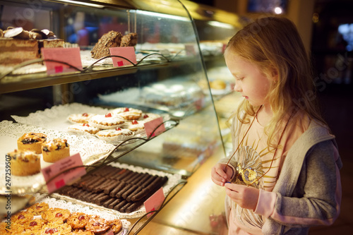Foto op Canvas Bakkerij Adorable little girl looking at fresh baked cookies on display in small store in Vilnius, Lithuania. Child choosing a dessert.