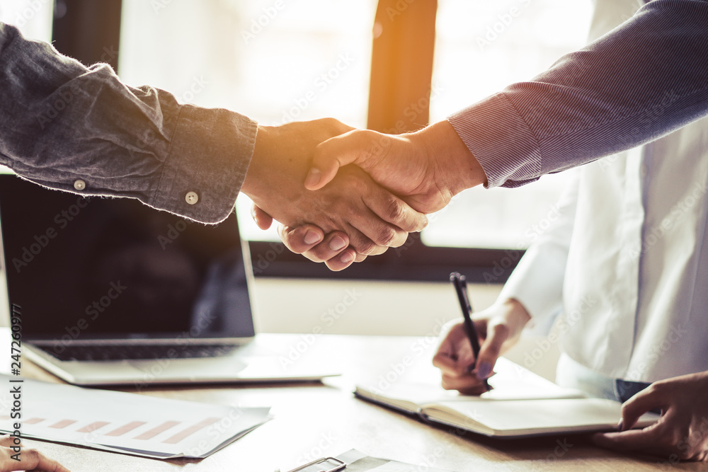 Fototapety, obrazy: Two businessmen handshaking in meeting after final project agreement deal done.