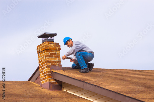 Contractor Builder with blue hardhat on the roof caulking chimney Fototapet