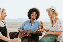 Friends Singing Together At A Beach Picnic