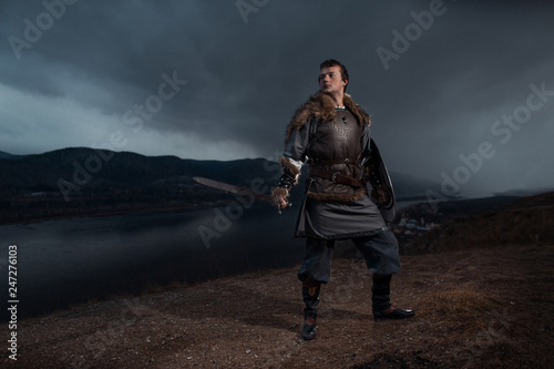 Photo  Medieval knight with sword and spear in ancient armour over Winter Landscapes