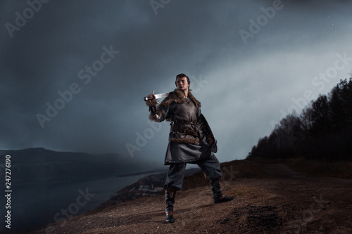 Vászonkép Medieval knight with sword and spear in ancient armour over Winter Landscapes