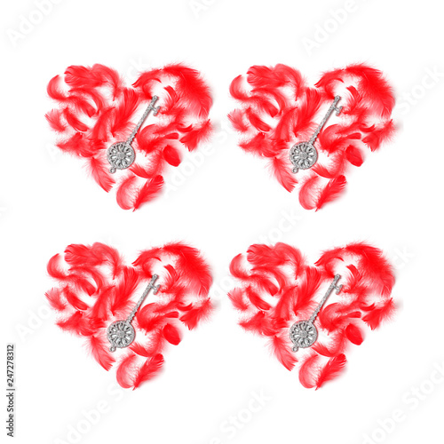 Fotografie, Obraz  symmetrical pattern of four red hearts laid out with feathers and keys on a white background