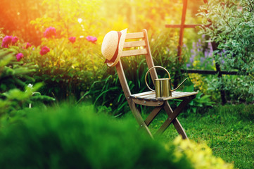 beautiful blooming summer private garden with wooden chair, gardener hat and watering can